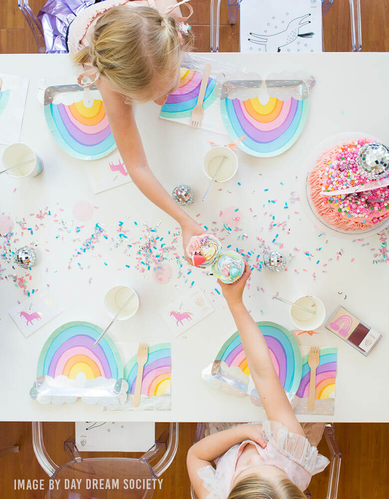 Girls celebrate a rainbow party with Day Dream Society over the rainbow die cut large paper plates and napkins, lots of rainbow color confetti