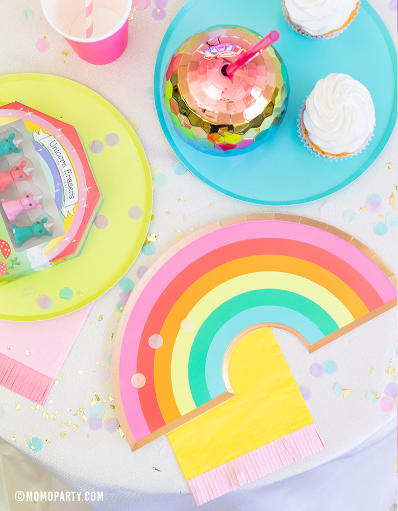 Rainbow party table view of Oh happy day rainbow plate, on top of yellow pink Hip Hip Hooray Fringe Small Napkin, cupcakes, Rainbow Ombre Disco Ball Tumbler on top of Oh happy day Rainbow Large plates, rainbow color paper cups, confettis, Mini Unicorn Erasers as party favor for a rainbow themed birthday party