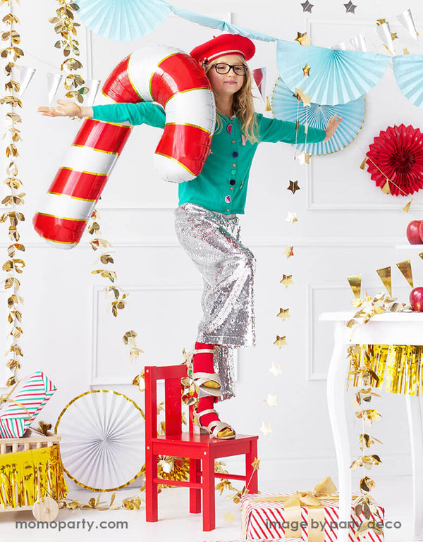 "A little girl carries party deco's 32"" red candy can foil balloon playing balance in a Christmas themed party with festive Christmas decorations including gold star banners, light blue bunting garlands and red paper fans around her"