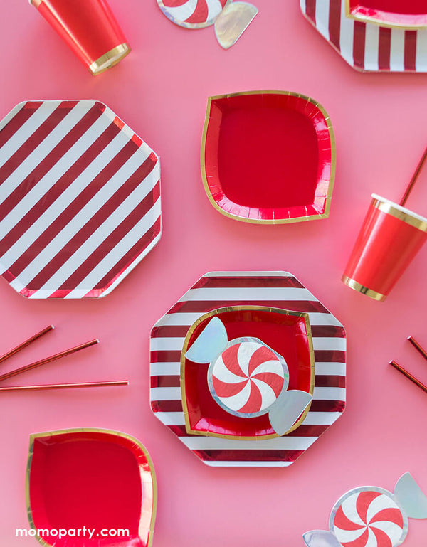 "Pink & Red holiday party table set up with Jollity & Co Red 6"" Christmas Peppermint Small Napkins, Posh Ruby Kiss Dessert Plates, Red stripe dinner plates, Posh Ruby Kiss Cups with red party paper straw on a pink background, for a sweet holiday celebration"