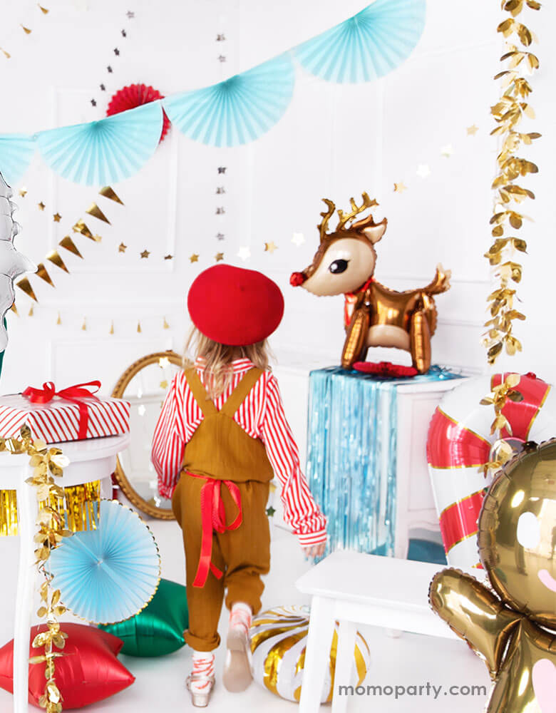 A little girl walking into A Christmas party set up filled with festive Christmas foil balloons including reindeer balloons, candy cane balloons and gingerbread man balloons