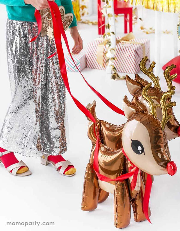 "A Kid in festive Christmas sequin outfits walking party deco's 24"" Reindeer Foil Mylar Balloons with Christmas gifts in the background"