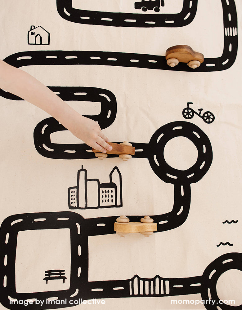 A top view look of A Boy's arm play with his wooden car toys on Imani Collective interactive play floor mat - Road Floor Mat. This floor mat is natural canvas hand with black screen printed road bike, houses modern illustration, Sewn and screen printed by hand on natural canvas by Kenyan artisans. Sold by Momo party store provided modern party supplies, boutique party supplies