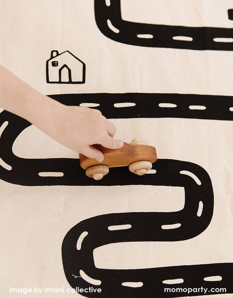A close up look of A Boy's hand holding a wooden car toy on Imani Collective interactive play floor mat - Road Floor Mat. This floor mat is natural canvas hand with black screen printed road bike, houses modern illustration, Sewn and screen printed by hand on natural canvas by Kenyan artisans. Sold by Momo party store provided modern party supplies, boutique party supplies