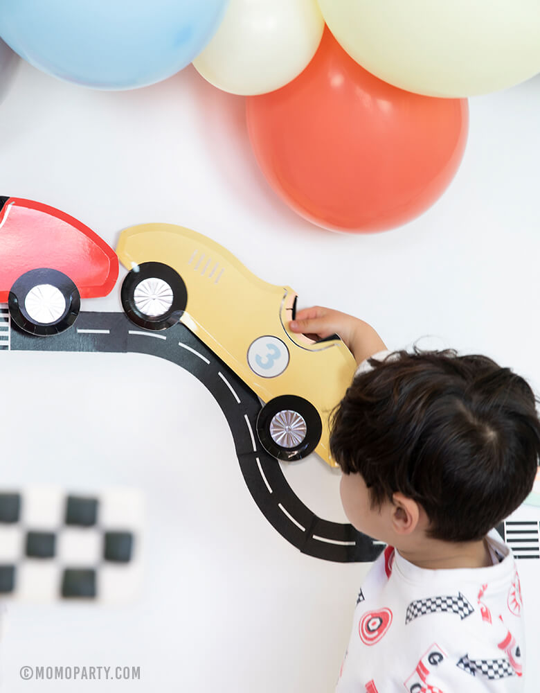 boy play with MeriMeri Car Plate with Road tape decorated as backdrop with matt blue, coral, matt yellow balloon garland in a race car birthday party