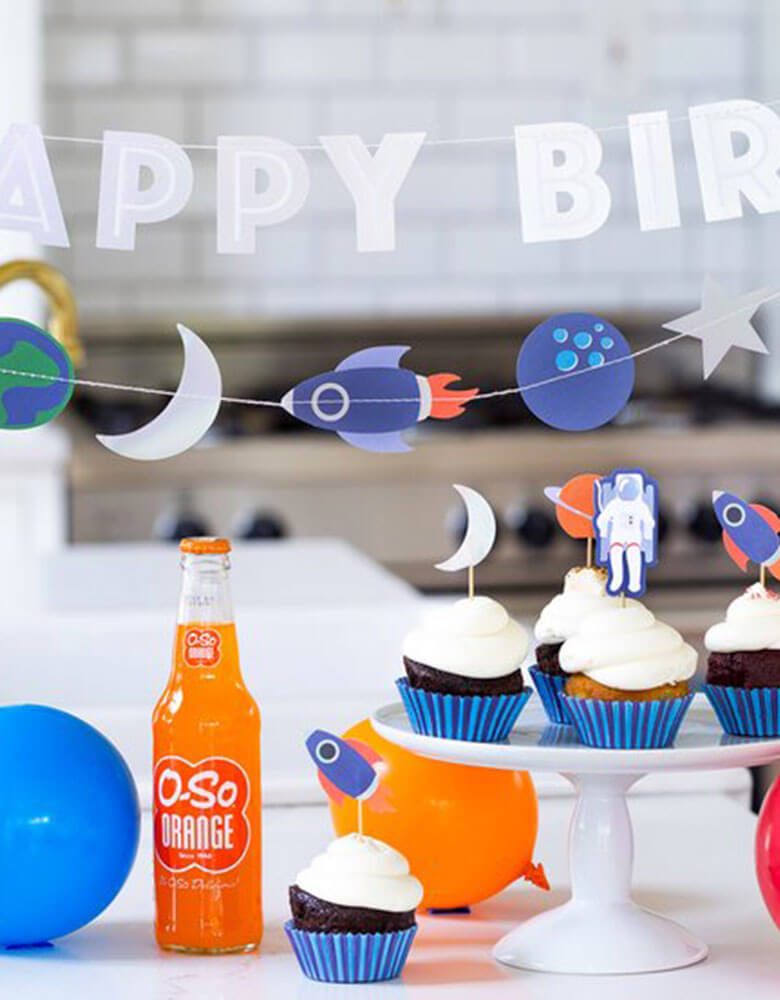 A space themed kids birthday party with My Minds Eye Rocket-Space-Mini-Banner and Happy Birthday Banner on the back with cupcakes decorated with space themed toppers
