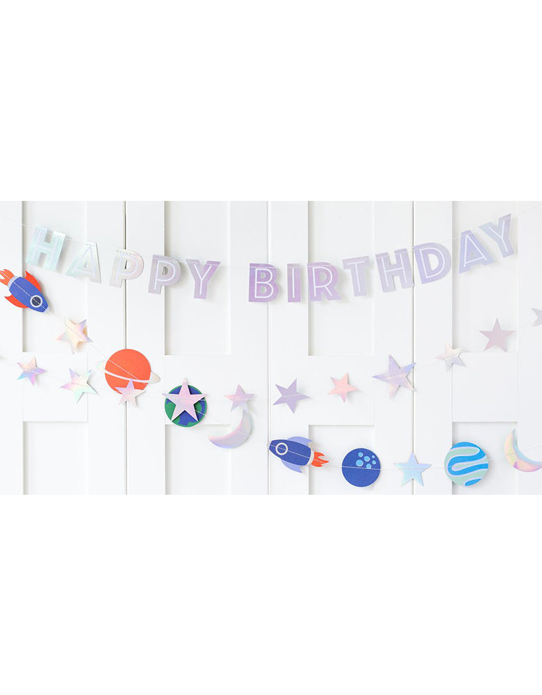 A kid's space themed party with 3 sets of space themed Banners on the wall featuring Happy Birthday message with planet, star, moon, sun, and rocket designs