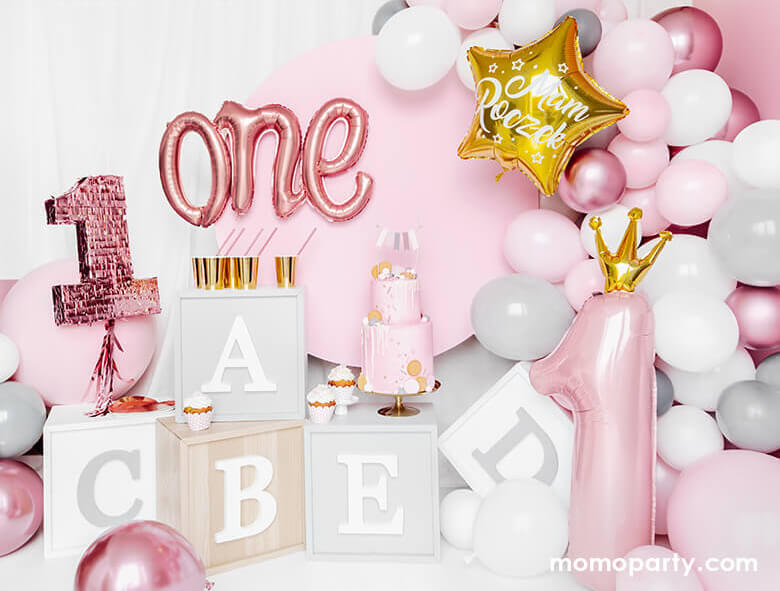 Adorable first birthday party decorated with Alphabet letter blocks, Rose Gold One Script Foil Balloon, a 2 tire pastel pink cake with flag topper, cupcakes, lots of pink and white latex balloons, and a 35 inch Little Crown Number 1 Pastel Pink Foil Balloon by Party Deco on the side. This adorable party set up is prefect for your baby first birthday party, baby 1st year's photoshoot, 1st year celebrations! It's a great way mark your little princess' big milestone!