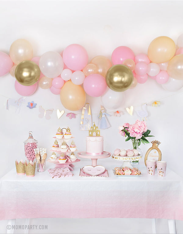 Royal Princess party dessert table with backdrop decoration idea, feathered a Diy balloon garland made with Qualatex latex balloons, Meri Meri Magical Princess Garland. On the dessert table, a Pastel pink cake with Princess Castle Cake Topper on top, Meri Meri Blushing Heart Plates layered with Blush Large Plates in the middle, Day Dream Society Sweet Princess Cups and Napkins on the side, Cupcakes with Princess Castle Cupcake Toppers on pink cake stand. for Royal princess birthday party celebration