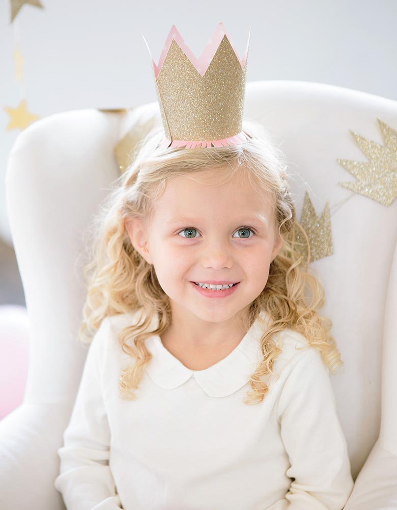 little blond girl wearing my mind's eye Princess Crown Party Hats with gold glitter finish and pink paper fringe in a princess birthday party