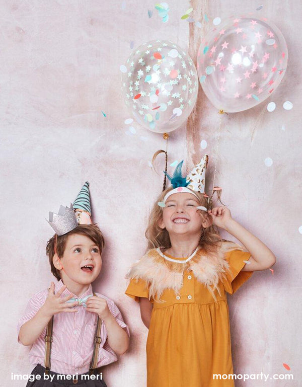Boy and Girl having fun by dress up with feature and fun Meri Meri Party Hats with confetti balloons