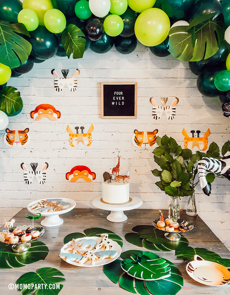 "Safari Jungle Birthday Party desert table with safari themed balloon garland and Talking Tables, Party Animals Paper Masks of Zebra, Giraffe, Tiger and Monkey and letter board of ""Four ever wild"" sign as backdrop wall decoration."
