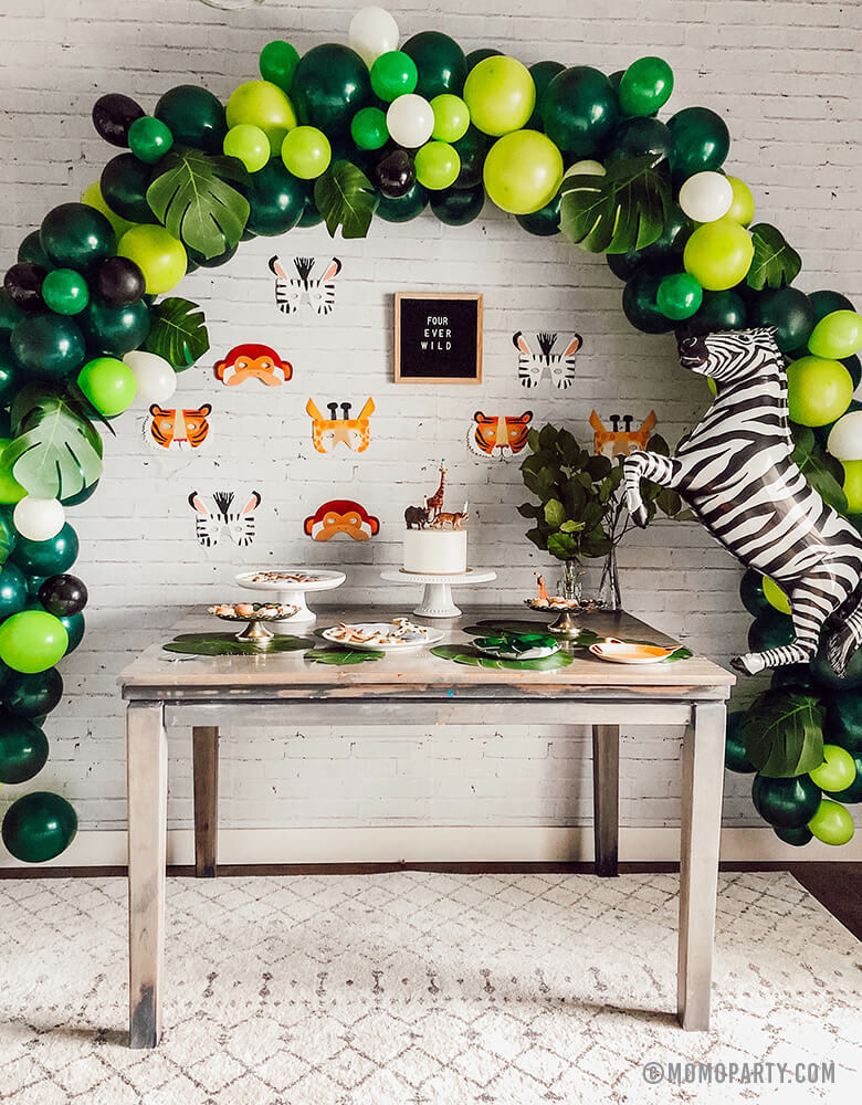 "Safari Jungle Birthday Party desert table with safari themed balloon garland and Talking Tables, Party Animals Paper Masks of Zebra, Giraffe, Tiger and Monkey and letter board of ""Four ever wild"" sign, Zebra foil balloon on the side as backdrop wall decoration."