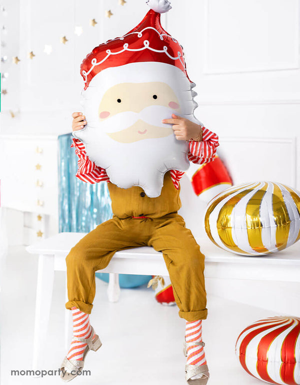 "Kids Christmas Party Ideas by Momo Party featuring Party deco's 24"" Santa head foil balloon held by a little girl sitting on a festive table with Christmas decorations around her"