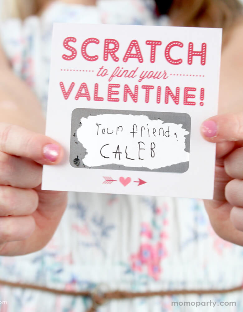 "A girl holding a inklings Paperie Scratch-off-Valentines-Card, with scratched off from the her valentine gift from her friend, with a handwritten note of ""your friend, Caleb"" message in the blank area, Super cute card for Valentine's card exchange for the little ones, school Valentine's card exchange, Valentine's day activities, galentine's day gift"