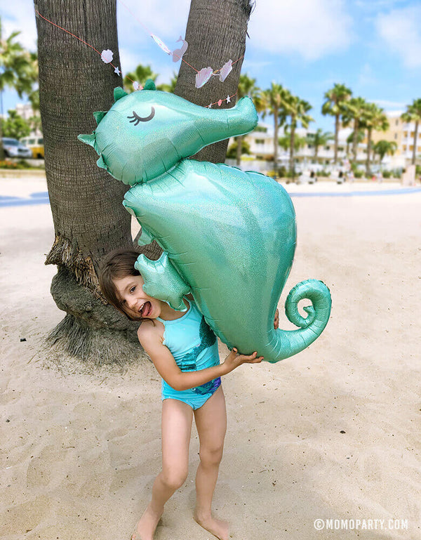 Girl holding Giant Seahorse Holographic Foil Balloon on the beach