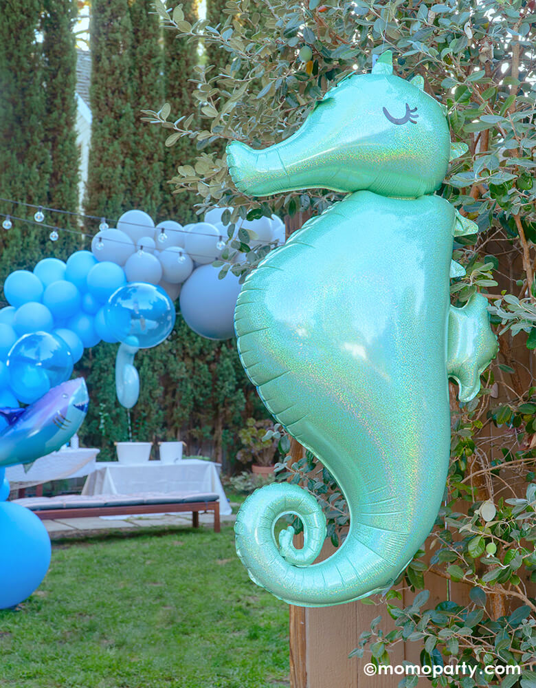 under the sea themed party at outdoor yard, a Seahorse Holographic Foil Balloon hanging in front of the entry door to welcome the guest, a blue colored balloon garland with shark foil balloon in the yard for a sea friends themed birthday party