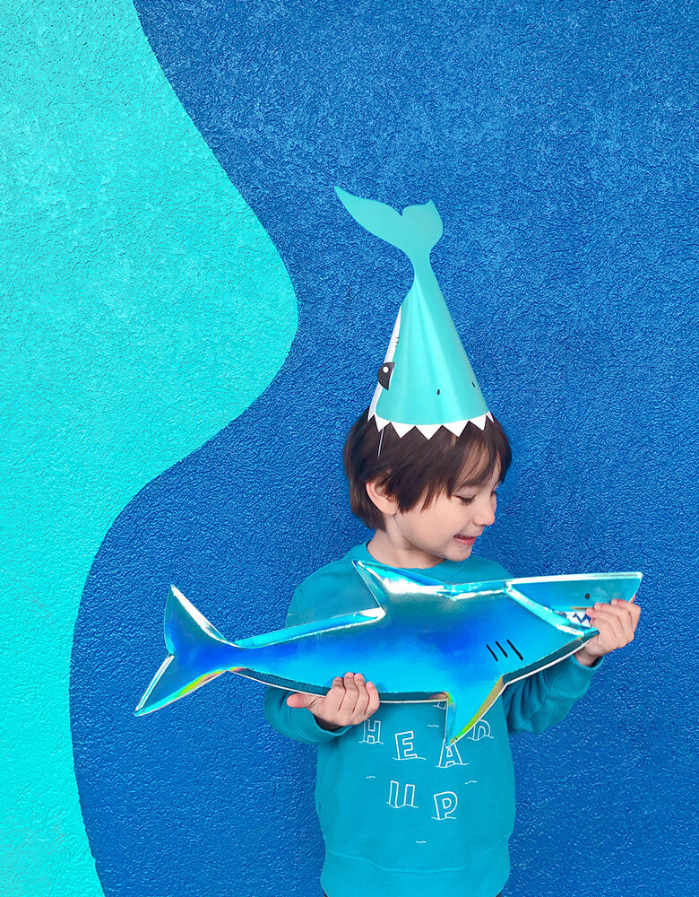 boy with shark party hat and holding shark plater