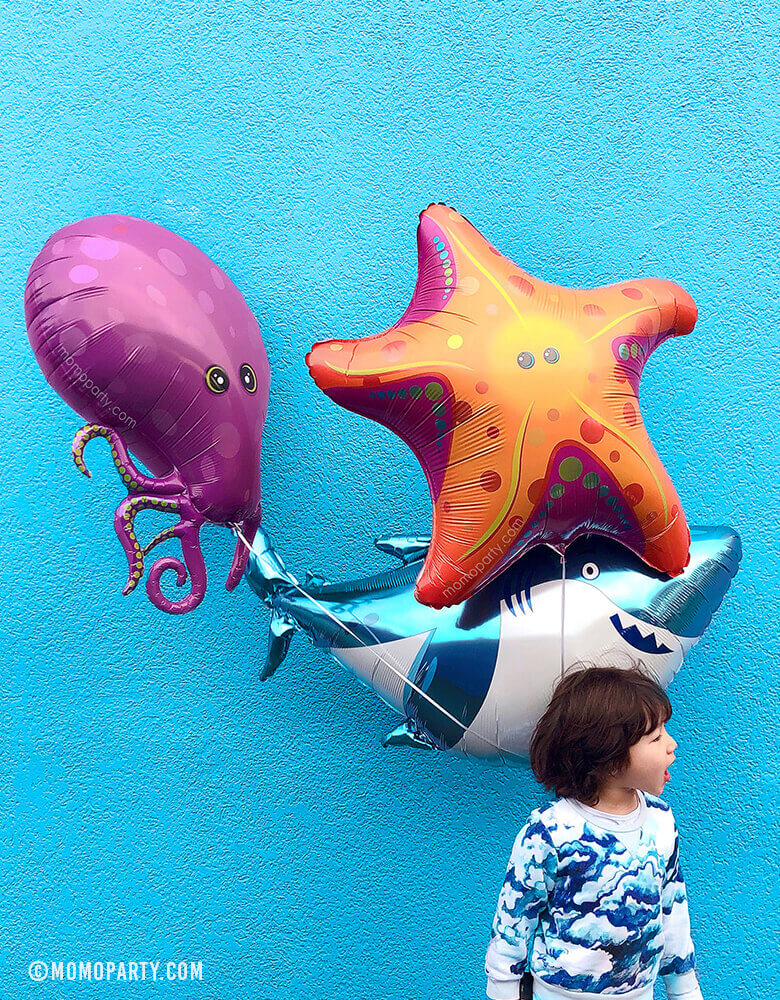 boy holding Shark, purple Octopus and StarFish Foil Balloons