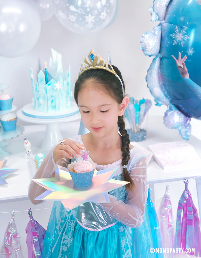 Elsa princess holding a cupcake on Meri Meri 8-point Shining Star Plates in a Frozen birthday party