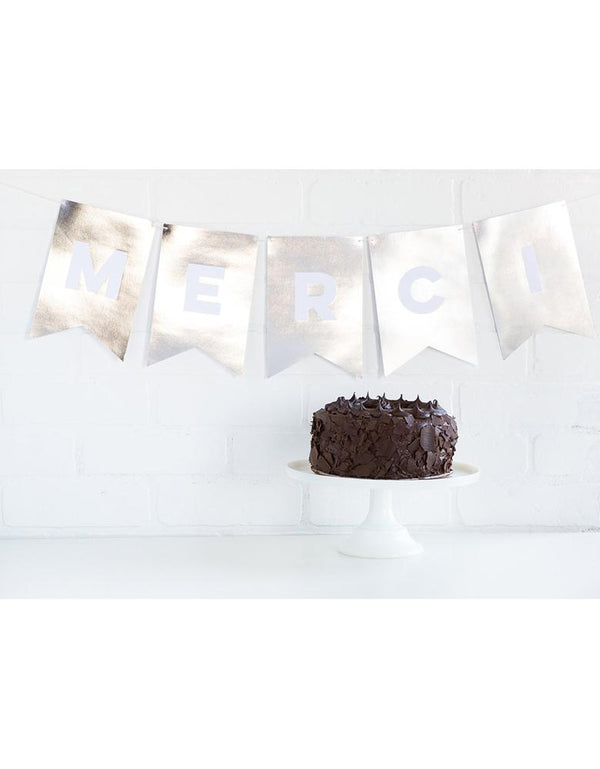 My Minds Eye Paperlove Silver Letter Banner with Merci spelled out on the wall with a chocolate cake on the table