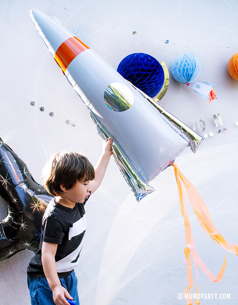 Boy holding Meri Meri Rocket Mylar Balloon with space garland and number 4 black star foil balloon for his 4 yrs old Space Blast Off birthday party