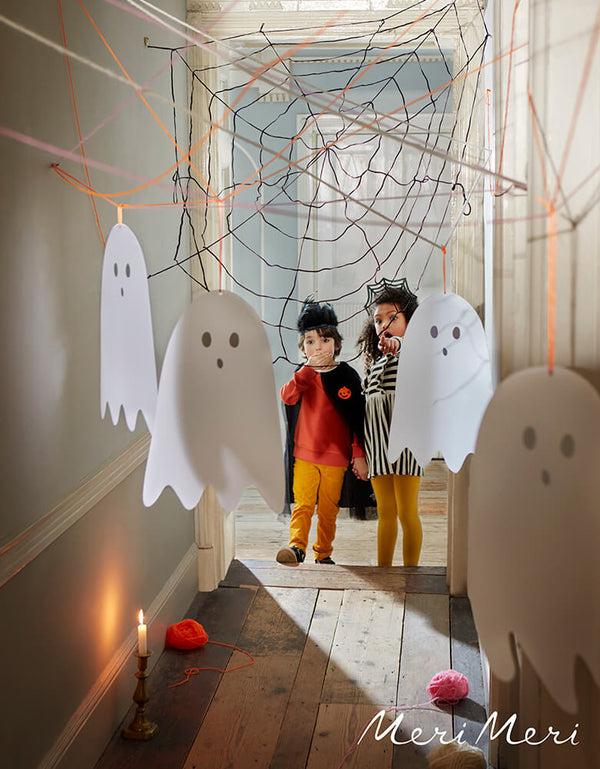 Kids standing in the hallway with hanging ghost and spider web decorations, These Meri Meri Spooky Ghost Decorations, come in pack of 10 with 3 sizes Ghost. These eerie translucent ghost decorations, with shimmering silver holographic foil mouths and eyes. Each has a bright orange cord that makes them easy to hang and looks fantastic for your modern spooky halloween party, trick-or-treating halloween party, nightmare before christmas party, witch themed party and all halloween related celebrations