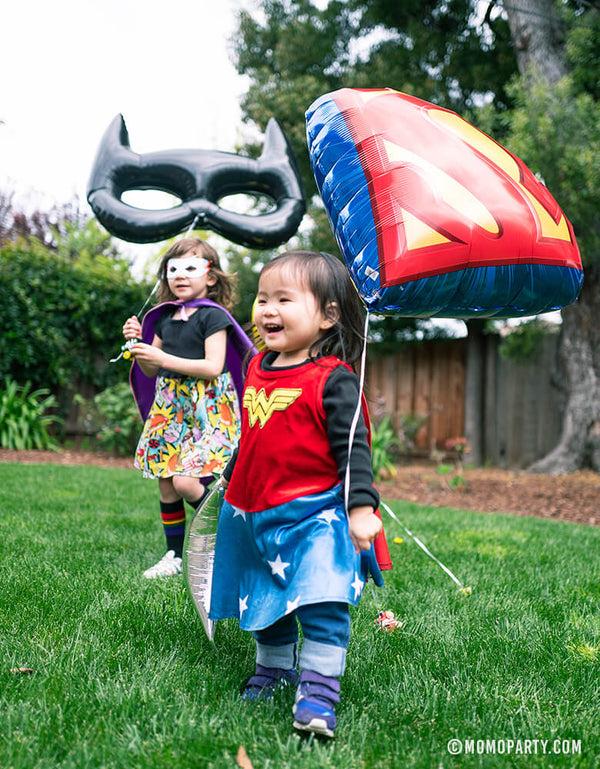 little girl wear wonder woman costume holding a Superman Emblem Foil Balloon with another girl holding giant black bat mask shaped foil balloon in a kid superhero birthday party