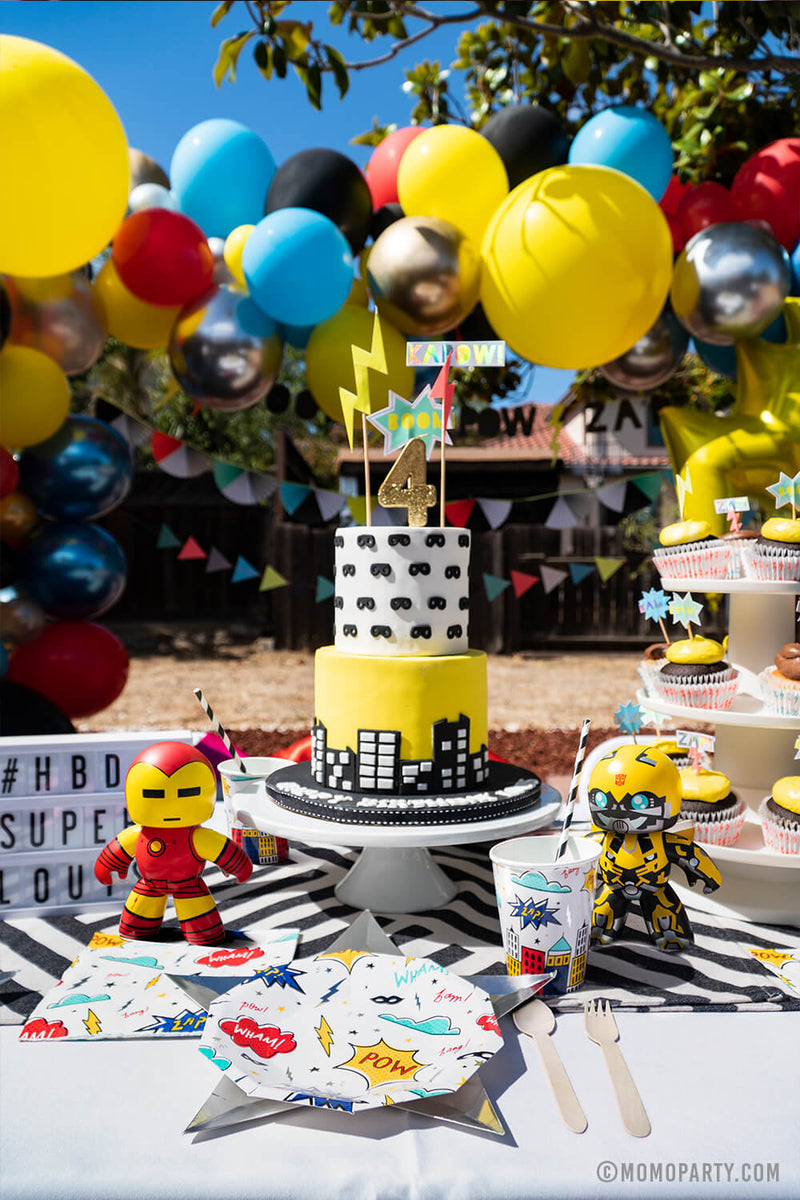 Kids modern superhero birthday party table set up with Day Dream Society Superhero Party Small Paper Plate, Star Silver Foil Plate, Superhero Napkins, and wooden utensil, Modern Superhero cake with number 4 gold glitter candle,  superhero sign cake topper, balloon garland as decoration on the back