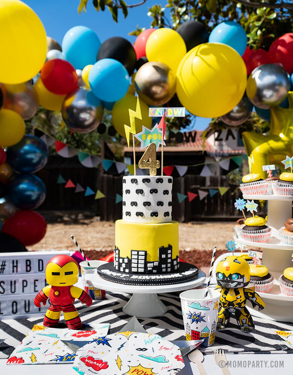 Kids modern superhero birthday party table set up with Day Dream Society Superhero Party Small Paper Plate, Star Silver Foil Plate, Superhero Napkins,superhero cup and wooden utensil, Modern Superhero cake with number 4 gold gilter candle, superhero sign cake topper, superhero figure toys, balloon garland as decoration on the back
