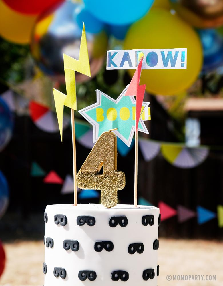 "Super Hero themed Birthday Cake design with MeriMeri Zap! Superhero Cake Toppers of Bright Cosmic sign, lighting bolts and  superhero-themed headlines ""Boom"" 'Kapow!"" and Talking Tables We Heart Birthday Glitter Candle - Goldgold glitter dipped number 4 candle for 4 years old boy's modern superhero birthday party"