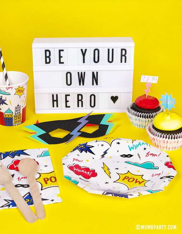Kids superhero themed birthday party table set up with Day Dream Socity Superhero Small Plates and cups, meri meri superhero paper masks, cupcakes, Be your own hero letter sign