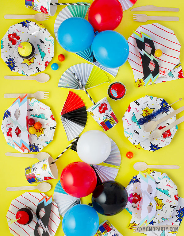 Kids superhero themed birthday party table set up with daydream society superhero plates and cups, colorful balloons as centerpiece