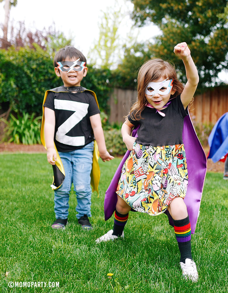 Boy and girl wearing Meri Meri Super Hero Masks  and capes in a outdoor superhero birthday party. girl power birthday party. girl superhero party