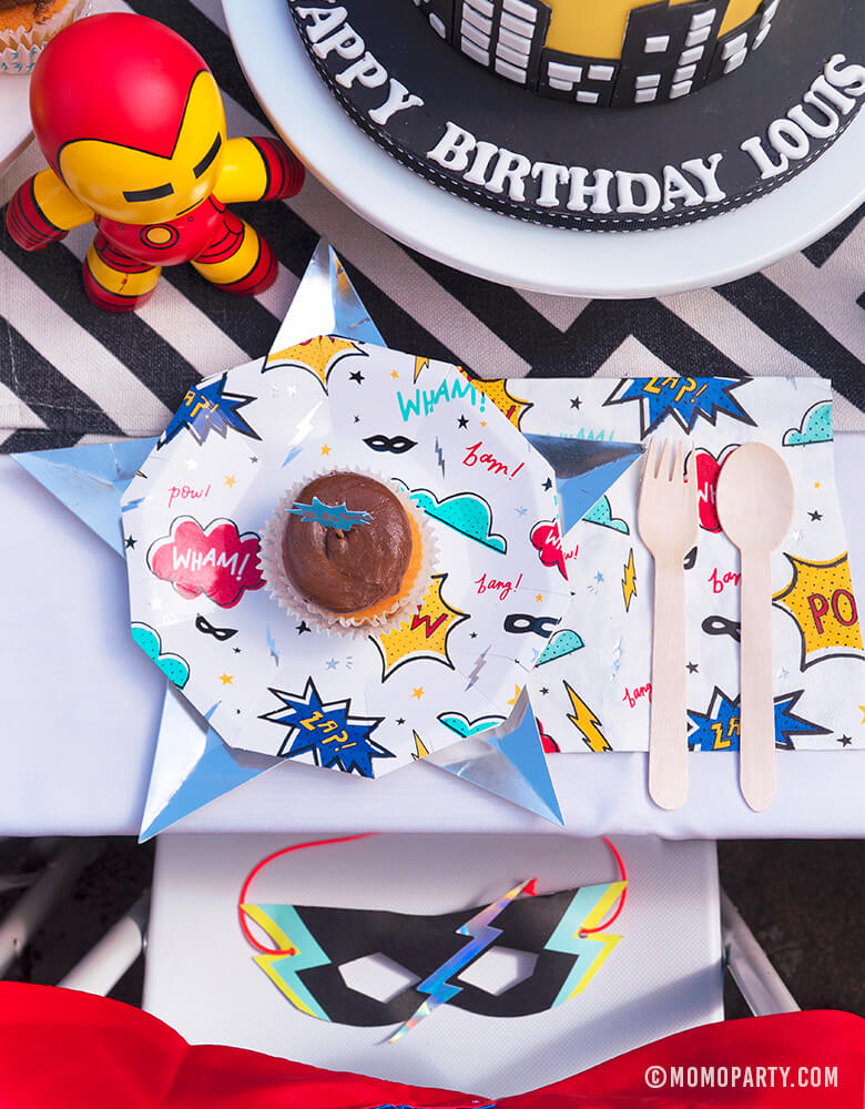 Kids modern superhero birthday party table with Day Dream Socity Superhero Party Small Paper Plate, Star Silver Foil Plate, Superhero Napkins, and wooden utensil, a Superhero Mask on the chair