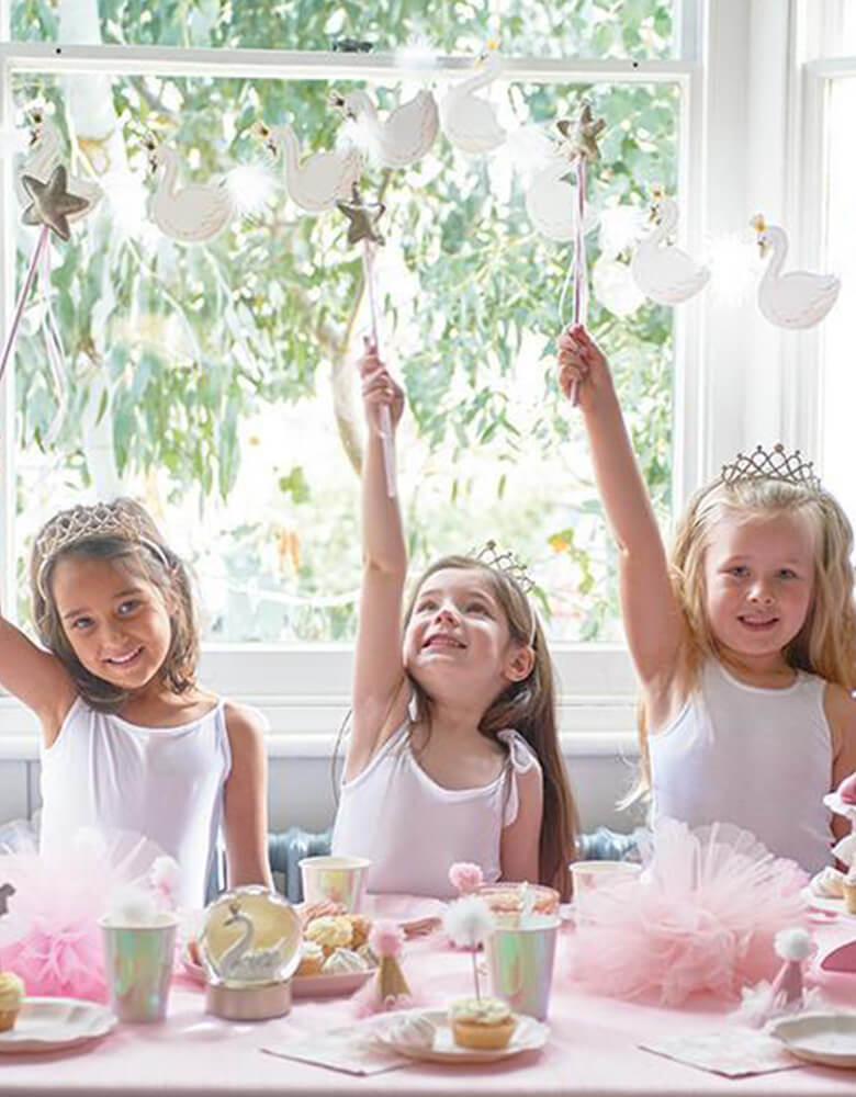 Girls raising star wand with swan garland on the back