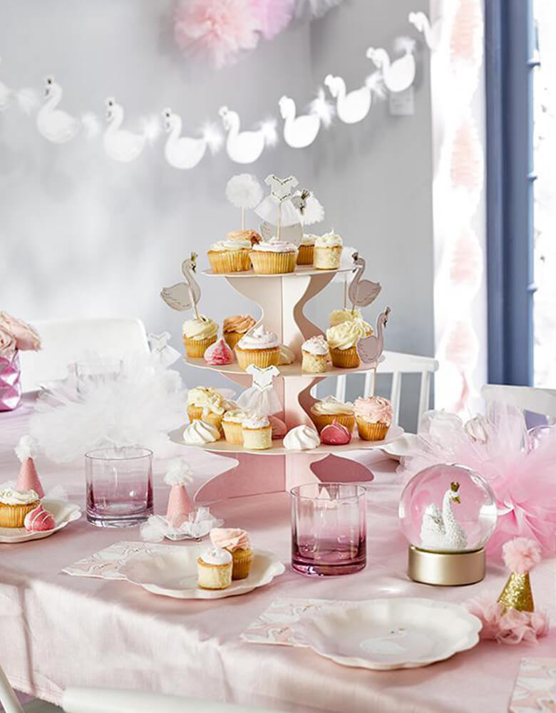 Swan Princess party table set up inspiration with We Heart Swan Hanging Garland, Swan plates, cupcake on a pastel pink cupcake stand, swan snow ball on the table as decoration