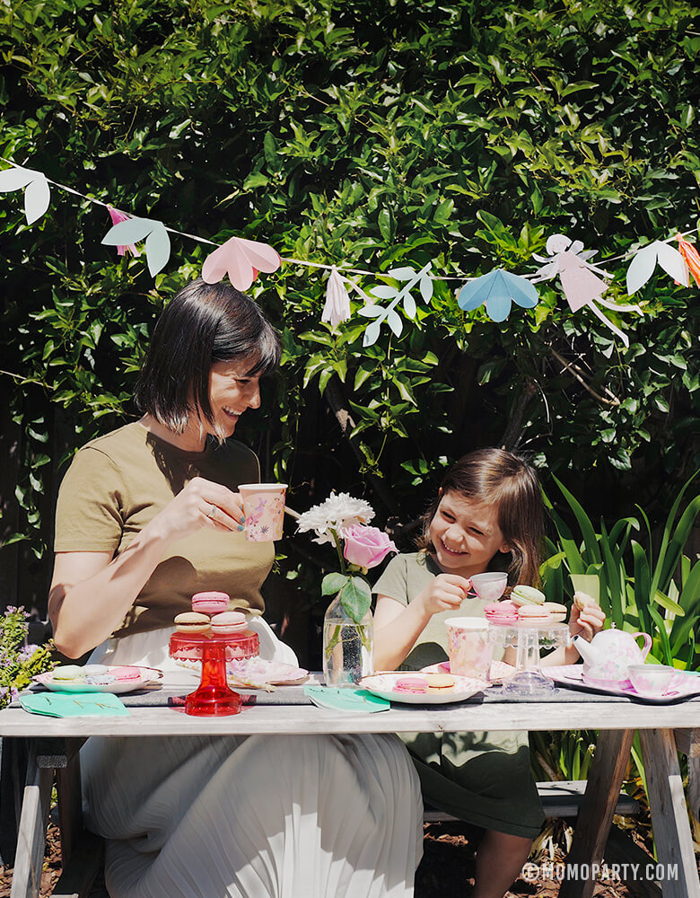 Happy moment of Mother Daughter Mother's day Tea Party celebration with MeriMeri-Fairy-Garland with fairy pennants, flowers, Talking Tables' Blossom Girls Small Plates and cups