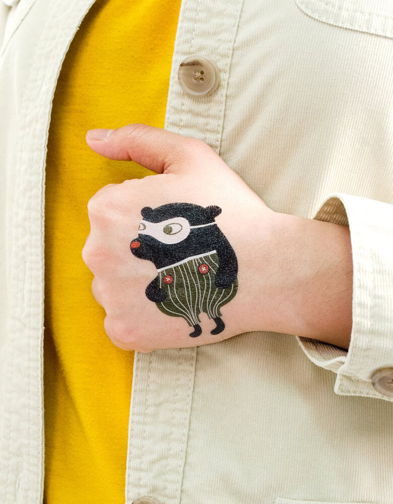 kid wearing Fair Bear Tattly safe and non-toxic Temporary Tattoos of Zoo Crew Set By Helen Dardik on his hand at party