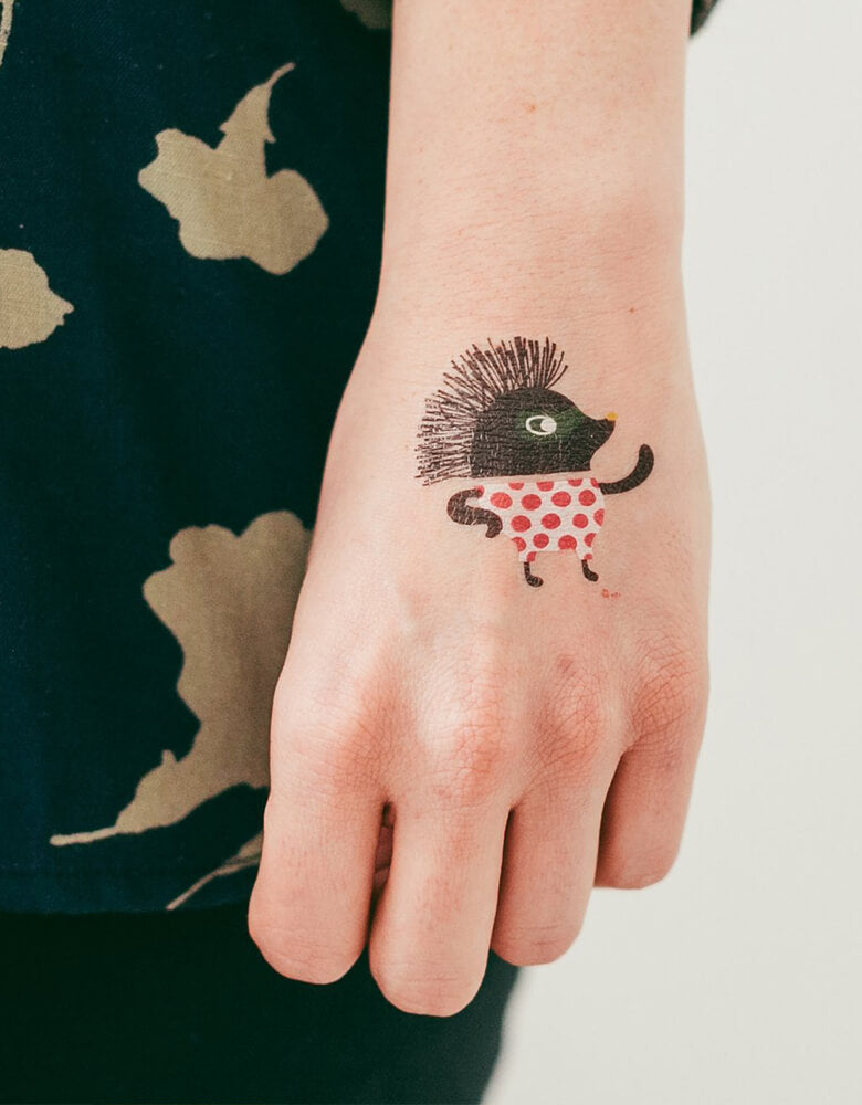 Girl wearing Fine Porcupine Tattly safe and non-toxic Temporary Tattoos of Zoo Crew Set By Helen Dardik on her hand at birthday party