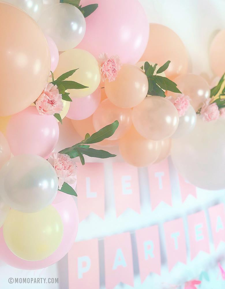 "A beautiful pink blush pastel balloon garland with flower decoration and Pink letter banner of ""Lets Partea"" for a floral pastel tea party birthday celebration"
