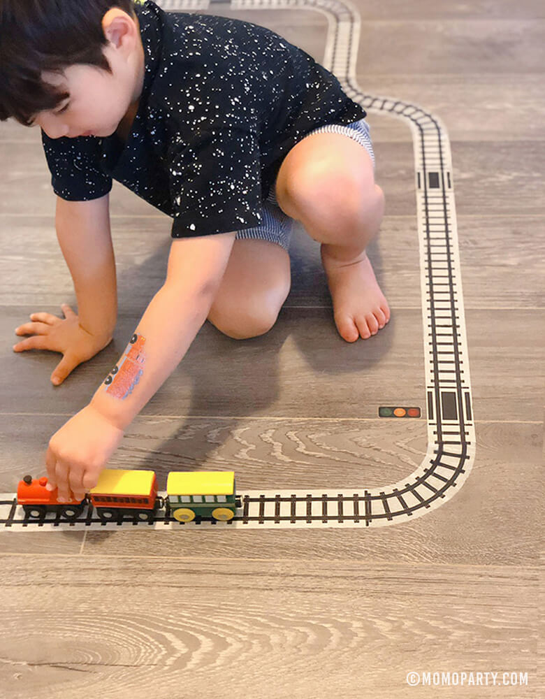 Boy playing train wooden toys on Train Track Tape on the floor