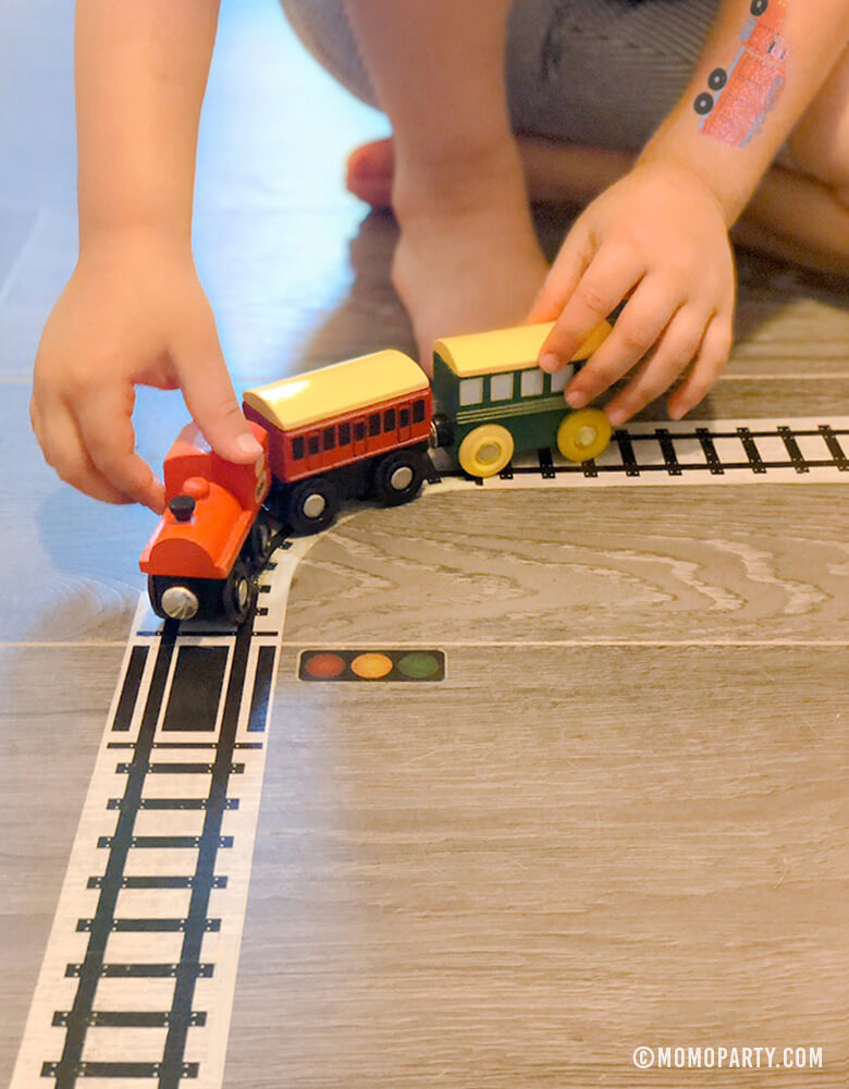 Kid play train wooden toy on Train Track Tape on the floor