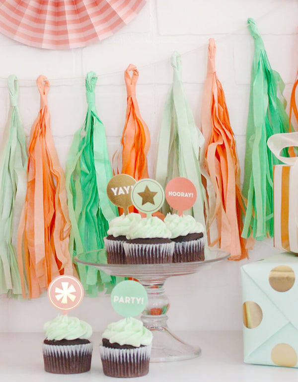 "A modern Birthday party with Trend Tassel Banner in peach, mint and coral colors hung on the wall and mint cupcakes with ""yay"" ""Hooray"" ""Party"" cupcake toppers on the table with birthday gifts wrapped in mint dotted paper"