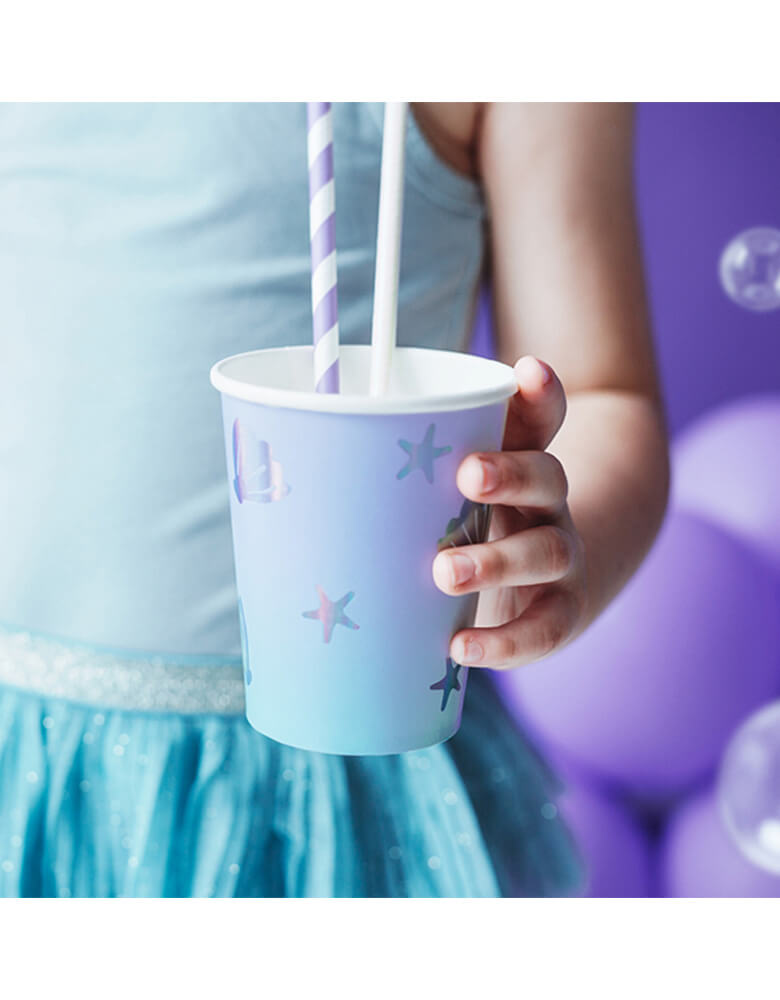 Kid's holding a Party Deco Under The Sea Cup in front of a lilac mermaid backdrop