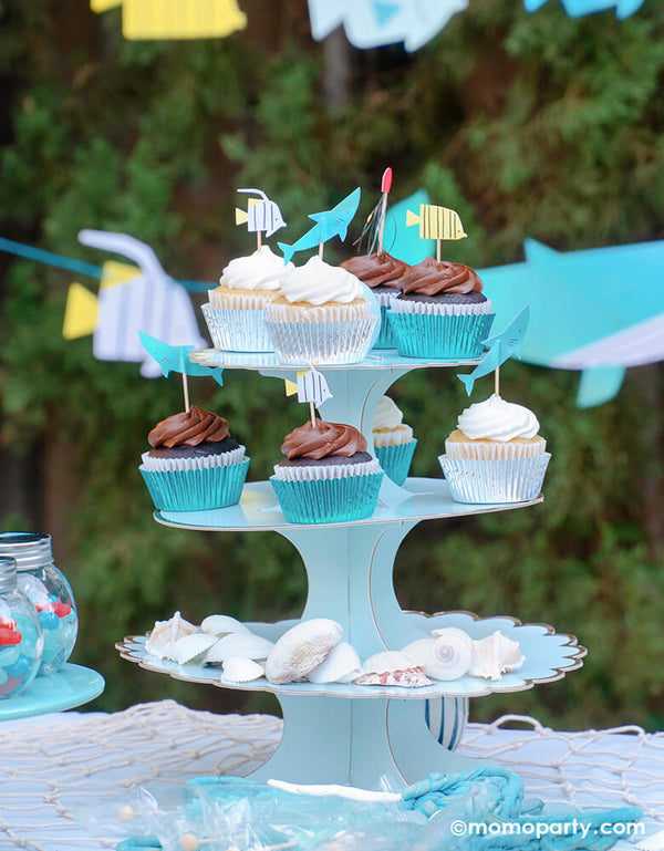 Under the sea party table idea. cupcake decorated with Under The Sea Cupcake Kit, on a 3 tier light blue cake stand. the bottom tire decorated with sea shells. These beautifully crafted toppers of sea friends like shark, fish, jellyfish and coral, takes on an underwater adventure sea themed party celebration! Party set up, partywares and Photo by Party Boutique Online at momoparty.com