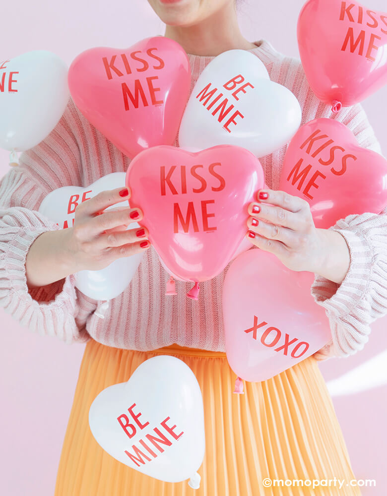"Girl holding a ""Kiss me"" mini Conversation Heart Shaped Latex Balloon, with lots of Qualatex pink, rose and white conversation heart balloons on her pink sweater and yellow dress in a pink background to celebrate valentines day"