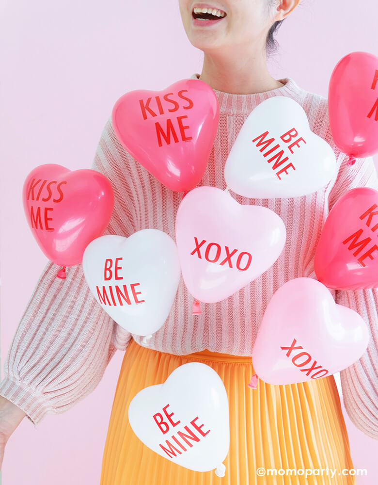 Girl dance with lots of Qualatex pink, rose and white conversation heart balloons on her pink sweater and yellow dress in a pink background to celebrate valentine's day, galentine's day
