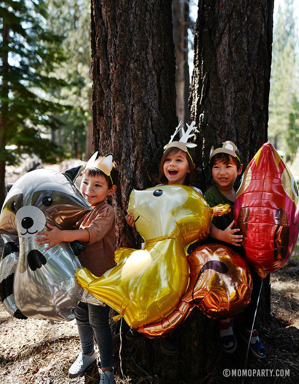 Kids holding raccoon, Owl and Squirrel Foil Mylar Balloon in the forest