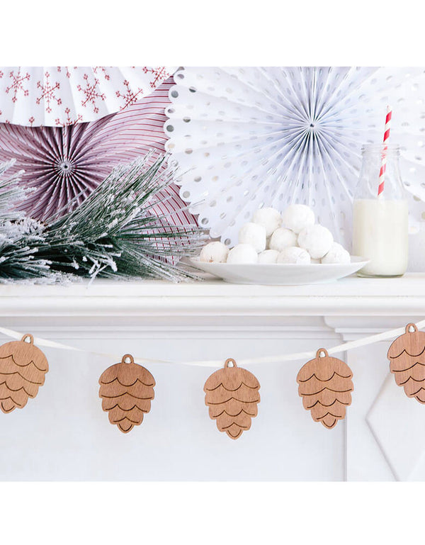 A beautiful white mantel decorated with Christmas themed paper fans and my mind's eye wooden pinecone banner